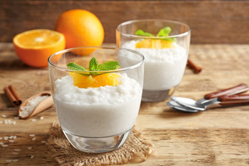 Creamy rice pudding with orange on wooden table