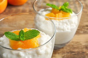 Fototapete - Creamy rice pudding with orange in glasses on table, closeup