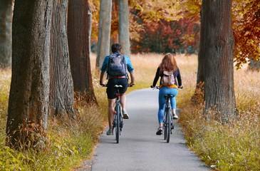 Junges Paar fährt durch ein herbstliches Waldgebiet Fahrrad