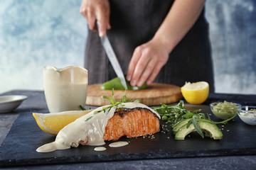 Slate plate with salmon and delicious sauce and blurred woman cutting avocado on background