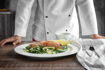 Plate with tasty salmon and female chef on background