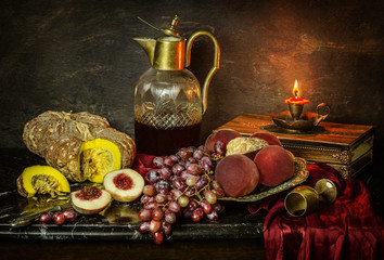 Classic still life with fresh delicious grape placed with peaches,pumpkins,illuminated candle and drink on black marble table