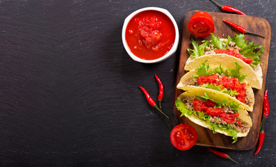mexican tacos with meat and salsa on a dark background