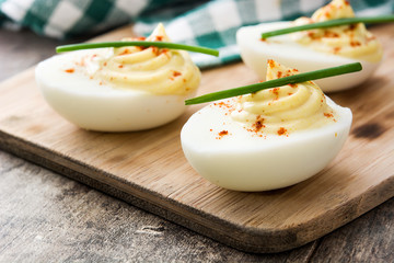 Stuffed eggs with mustard,mayo and paprika  on wooden table