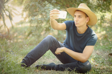 Young handsome man taking a selfie, sitting in the grass in the countryside