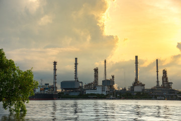 Oil Refinery Industry Plant in Bangkok, Thailand with cloudy sunrise background. Conventional energy concept.