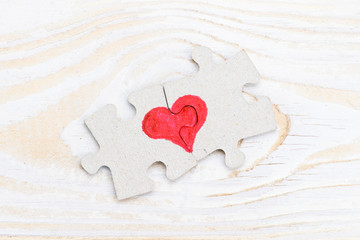 Heart made of two pieces of jigsaw puzzle on light wooden table, close-up