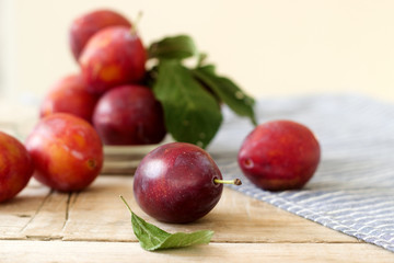 Plums in a plate on a wooden table, rustic style, selective focus.