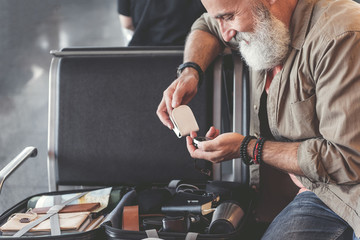 Cheerful grandfather watching at compass in airport