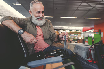 Outgoing pensioner watching at bag in airport