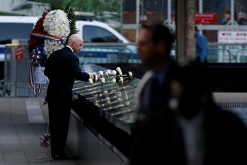 A man places white roses at the edge of the South reflecting pool at the National September 11 Memorial and Museum during ceremonies marking the 16th anniversary of the September 11, 2001 attacks in New York