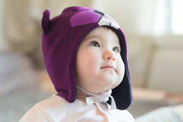 Little child in a beaver cap close up portrait.