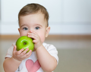 Little child with a green apple in his hands. Close up portrait.