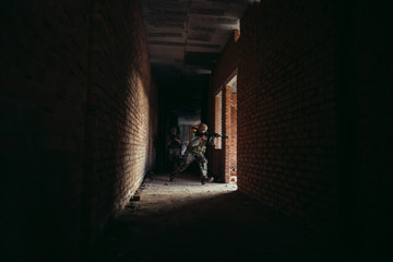airsoft soldiers with a rifle playing strikeball In an abandoned brick building