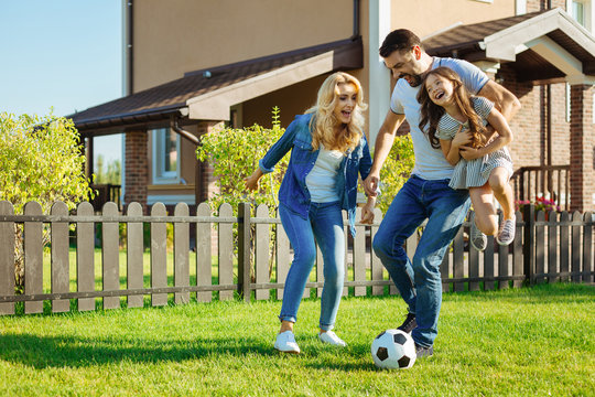 Loving father carrying daughter and playing football with family