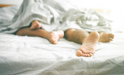 Close up of male and female feet on a bed - Loving couple having sex under under white blanket in the bedroom