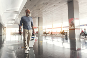 Assured smiling elder man walking through airport