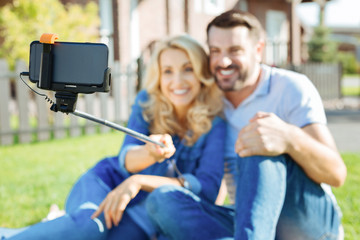 Cheerful couple taking selfies with a selfie stick