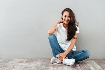 Joyful pretty asian woman sitting on the floor