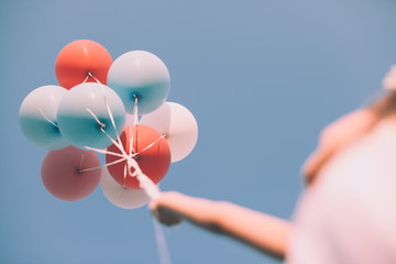 Girl holding colorful balloons up in the air - Low angle view