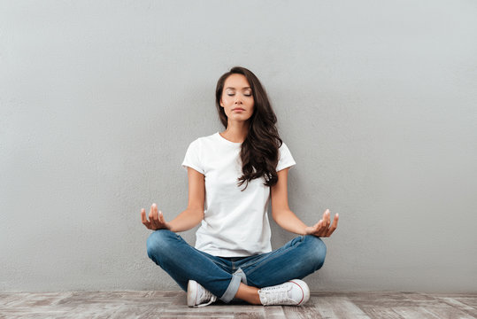 Beautiful young asian woman sitting in yoga position and meditating