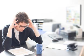 Junger Mann im Büro, überfordert