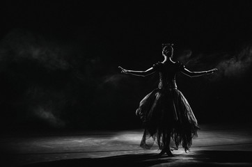 Light silhouette of elegant young ballerina standing back to camera in second position arms pose on the black background