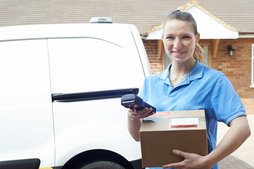 Portrait Of Female Courier With Van Delivering Package To House