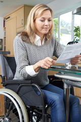 Disabled Woman In Wheelchair Reading Letter At Home
