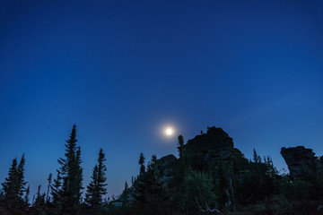 Stars and the moon against the backdrop of silhouettes of trees and rocks