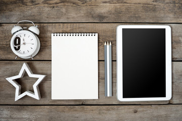 Modern conceptual wooden office or home desk table with tablet, note book, cup of pens, wooden star, businesscard and table clock. Place for typography and logo. Flat composition