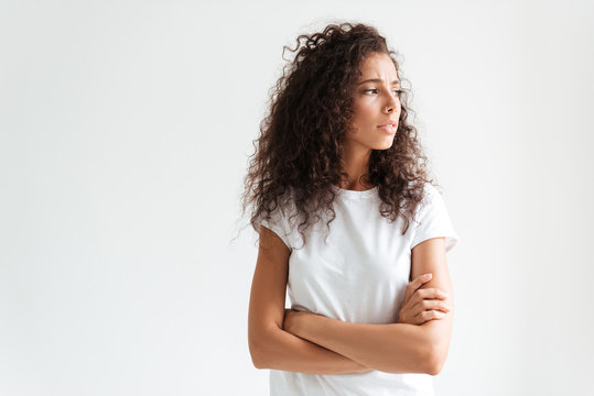 Upset young woman with curly hair standing with arms folded