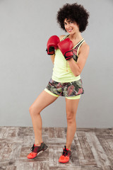 Full length image of Smiling sports woman in boxing gloves