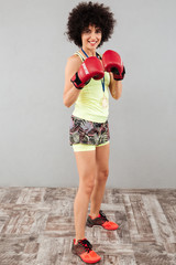Full length photo of carefree sports woman in boxing gloves