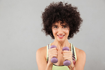 Close up picture of smiling curly fitness woman doing exercise