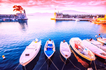 Nafpaktos bay, Greek small town, famous and popular travel destination with old castle at the bank of sea. Row of motor boats anchored in marine. Sunrise beautiful scenery.