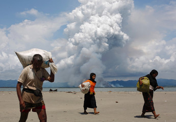 Smoke is seen on Myanmar's side of border as Rohingya refugees walk on the shore after crossing the Bangladesh-Myanmar border by boat through the Bay of Bengal, in Shah Porir Dwip