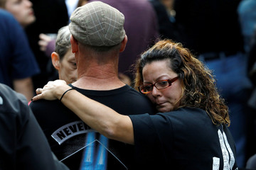 People embrace as they gather at the National 911 Memorial and Museum during ceremonies marking the 16th anniversary of the September 11, 2001 attacks in New York