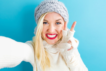 Young woman in winter clothes taking a selfie