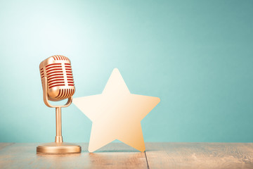 Retro golden microphone and star shape on wooden table front gradient mint green background. Vintage old style filtered photo