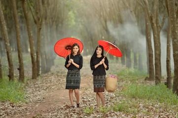 Two women walking along rural footpath, Thailand