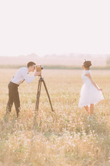 The side portrait of the vintage dressed newlyweds in the field. The groom is taking photos while the bride is posing.