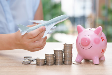 Holiday saving money with piggy bank and plane model - Stacking coins for traveling concept.