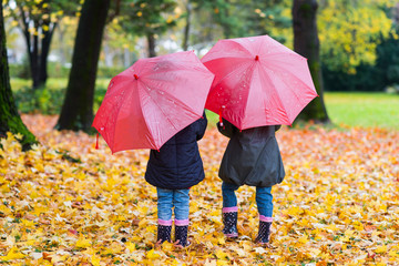 Little girls walking with red umbrella inthe autumn park