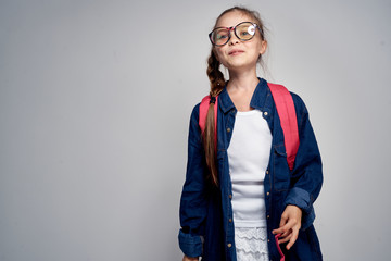 1451305 little girl in sunglasses, with a backpack, in a denim shirt