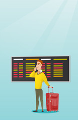 Young caucasian businessman looking at departure board at the airport. Passenger with suitcase standing on the background of departure board at airport. Vector cartoon illustration. Vertical layout.
