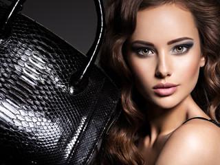 Beautiful woman with long hair holds black handbag