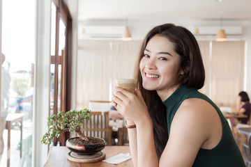 Young happy Asian woman drinking coffee in the coffee shop.