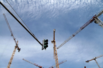 cranes and traffic light on blue sky