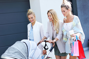 Trendy modern mother with friends outside with a stroller